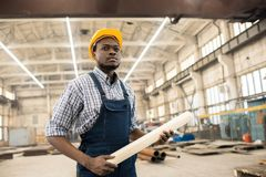 Confident African-American construction manager at workplace. Serious purposeful handsome young African-American construction engineer with beard wearing yellow stock images