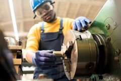 Machine Operator Adjusting Equipment. Confident African American machine operator wearing safety goggles and hardhat adjusting equipment while working at stock photography