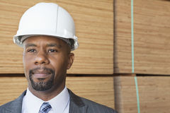 Confident African American male contractor looking away with stacked wooden planks in background Stock Photo