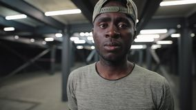 Confident african american man in cap at underground tunnel. Confident african american man in cap standing at underground tunnel gazing at camera stock footage