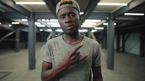 Confident african american man in underground tunnel gesturing cool sign stock video