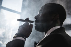 Confident african american man smoking cigar indoors. Side view of confident african american man smoking cigar indoors Stock Image