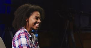 Casual black woman hosting TV show. Confident African-American woman in casual shirt sitting in spotlight in telecasting studio and talking while presenting stock video