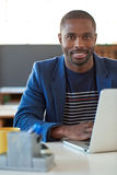 Confident African businessman working on a laptop in an office. Portrait of a confident young African businessman smiling while sitting at his desk in a large stock images
