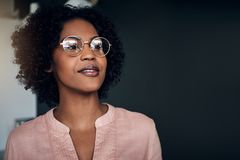 Confident African businesswoman standing alone in a modern office. Smiling young African businesswoman wearing glasses looking deep in thought while standing stock photos