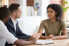 Confident african female applicant talking to diverse hr managers royalty free stock images