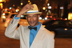 Confident African Man Holding Hat While Walking the City Streets at Night Royalty Free Stock Image