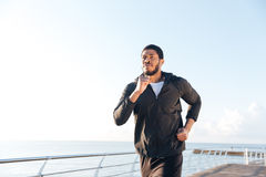 Confident african man listening to music and running on pier Stock Photography