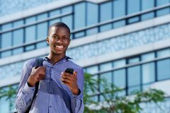 Confident african man smiling with mobile phone. Portrait of confident african male student smiling with mobile phone Royalty Free Stock Photos
