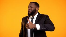 Confident afro-american businessman in suit making thumbs-up and winking, ad stock photos
