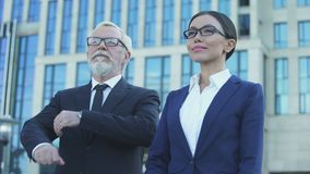 Confident aged and young business partners near office center, crossing hands. Stock footage stock video