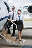 Confident Airhostess And Pilot Standing On Ladder Stock Image