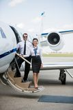 Confident Airhostess And Pilot Standing On Private. Full length portrait of confident airhostess and pilot standing on private jet's ladder at airport terminal Stock Photos