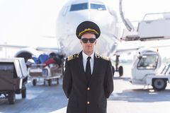 Confident airman ready for flight. Serious male pilot is standing afore aircraft. He wearing sunglasses and looking at camera. Waist-up portrait. Copy space Stock Image
