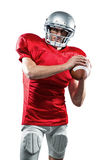Confident American football player in red jersey holding ball. On white background Royalty Free Stock Photography