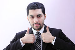 Confident arab business man with thumb up. Image of arab businessman wearing black suit and feeling confident with his success and raising thumb up Stock Image