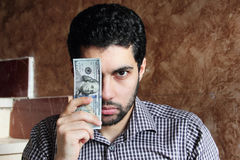 Confident arab young businessman with dollar bills money. Arab young muslim business man feeling confident with dollar bills on one of his eye Stock Image