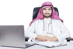 Confident Arabian doctor with laptop on desk Stock Photos