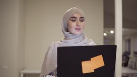 Confident arabic woman wearing beige hijab going by the hall while holding her black laptop in hands. Employee, working. Place, conference hall. Front view stock footage