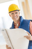 Confident Architect Holding Blueprint At Construction Site Royalty Free Stock Image