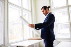 Confident architect holding blueprint Stock Image