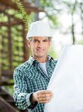 Confident Architect Holding Blueprint At Site Stock Images