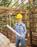 Confident Architect Holding Blueprint In Wooden Stock Photo