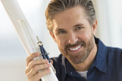 Confident Architect Holding Compass And Blueprint In Office Royalty Free Stock Image