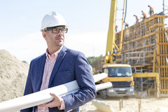 Confident architect holding rolled up blueprints at construction site Stock Image