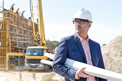 Confident architect holding rolled up blueprints at construction site Stock Photography