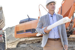 Confident architect looking away while holding blueprints at construction site Royalty Free Stock Images