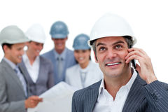 Confident architect on phone in front of his team Royalty Free Stock Photos