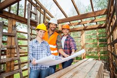Confident Architects Holding Blueprint In Wooden Stock Images