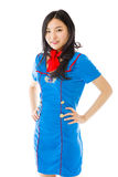 Confident Asian air stewardess standing with arms akimbo Stock Images