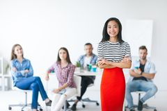 Confident asian business leader with her team on background. Crossed arms stock photo