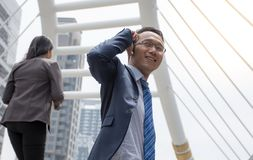 Confident Asian business man in suit looking away while standing outdoors with mobile phone Stock Image