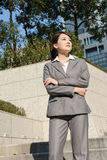Confident Asian business woman standing in outside of office in Stock Images