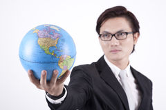 Confident Asian Businessman with Globe. Asian businessman looking smart with glasses holding a globe Stock Photography