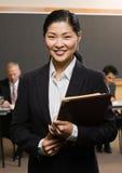 Confident Asian businessman holding files Stock Photos