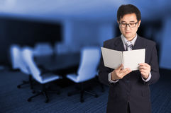 Confident Asian businessman reading notebook or document file in Stock Images