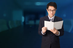 Confident Asian businessman reading notebook or document file in Royalty Free Stock Photography