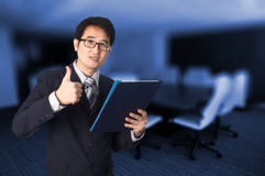 Confident Asian businessman showing document file and giving thu Royalty Free Stock Image