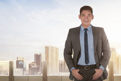 Confident asian businessman standing with hands in pockets. On cityscape background Stock Image