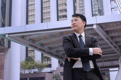 Confident Asian Businessman standing and looking at city for vis. Ion concept Stock Image