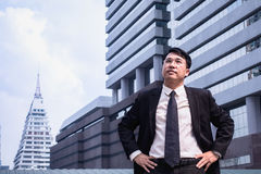 Confident Asian Businessman standing and looking at city for vis. Ion concept Royalty Free Stock Photo