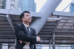 Confident Asian Businessman standing and looking at city for vis. Ion concept Royalty Free Stock Image