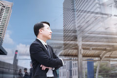 Confident Asian Businessman standing and looking at city for vis. Ion concept Stock Images