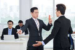 Showing Red Card to Subordinate. Confident Asian businessman wearing classical suit showing red card to his subordinate while standing at spacious open plan Stock Photos