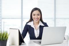 Confident asian businesswoman sitting by desk with laptop in office stock image