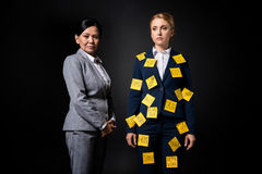 Confident asian businesswoman standing near stressed female colleague with sticky notes on clothes royalty free stock images
